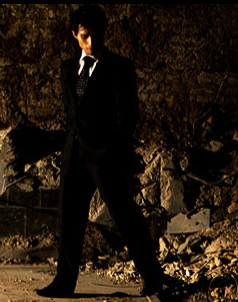 Fake Ben Corman standing in a fake suit among a fake building wreckage.